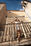 Young woman leaning against metal railings on old stone stairway Stock Photography