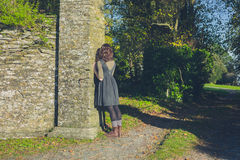 Young woman leaning against stone wall Stock Photo