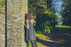 Young woman leaning against stone wall Royalty Free Stock Photo