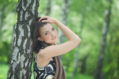 Young woman leaning against a tree Stock Photo
