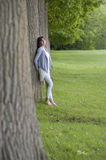 Young woman leaning against a tree Royalty Free Stock Images