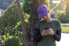 Young woman leaning against tree with staring mobile. stock photography