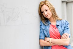 Young woman leaning against wall Royalty Free Stock Image