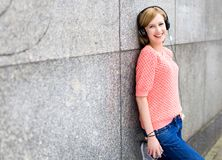 Young woman leaning against wall Royalty Free Stock Images