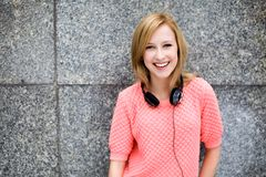 Young woman leaning against wall. Smiling young woman with headphones Royalty Free Stock Photo