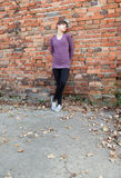 Young woman leaning against wall Stock Image
