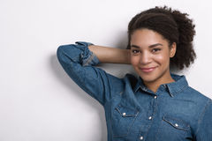 Young woman leaning against white wall. Hands behind head looking at camera royalty free stock photos