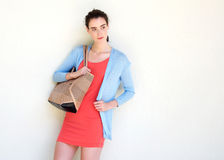 Young woman leaning against white wall with purse Stock Image