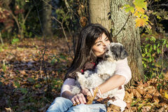 Young woman leaning on an autumn tree hugging her dog Stock Images