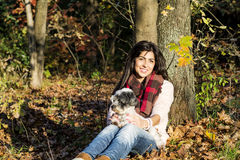 Young woman leaning on an autumn tree hugging her dog Stock Photo