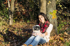 Young woman leaning on an autumn tree hugging her dog Stock Photos