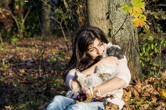 Young woman leaning on an autumn tree hugging her dog Royalty Free Stock Photography