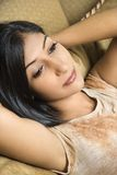 Young woman leaning back on sofa. Stock Photos