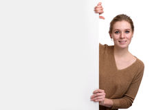 Young woman leaning on big blank board Royalty Free Stock Photo