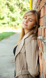 Young woman leaning on the brick wall in park Stock Image