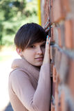Young woman leaning on the bricks wall Stock Image