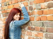 Young woman leaning on the bricks wall Royalty Free Stock Photos