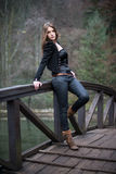 Young woman leaning at the bridge. Young woman in jacket leaning at the bridge Royalty Free Stock Images