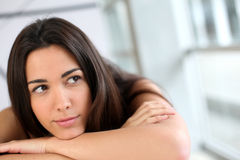 Young woman leaning on desk. Portrait of brunette with bored look stock photography