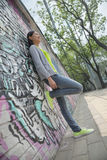 Young woman leaning and hanging out by a wall covered in graffiti Royalty Free Stock Photos