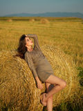 Young woman leaning hay stack enjoying breeze Royalty Free Stock Photos