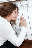Young woman leaning heating radiator Stock Photo