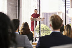 Young woman leaning on lectern presenting business seminar. Young women leaning on lectern presenting business seminar stock image