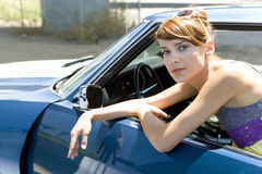 Young woman leaning on open door of car, portrait, close-up Royalty Free Stock Photography