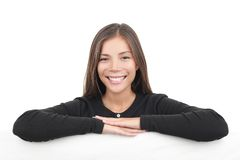 Young woman leaning over billboard banner. Mixed ethnicity chinese / caucasian model isolated on white background Royalty Free Stock Images