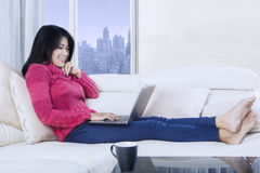 Young woman leaning on sofa with laptop stock images