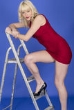 Young Woman Leaning on Step Ladder Wearing Short Red Dress Royalty Free Stock Photography