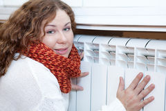 Young woman leaning to central heating con Royalty Free Stock Photography