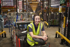 Young woman leaning on tow tractor in distribution warehouse royalty free stock photos