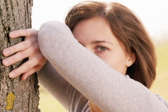 Young woman leaning on tree Stock Images