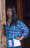 Young woman leans against doorway. A woman wearing a casual plaid shirt stands nect to a wooden post Royalty Free Stock Images
