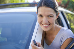 Young woman leans against her car Stock Photos