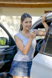Young woman leans against her car Royalty Free Stock Photo