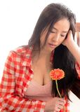 Young woman leans on a bench while holding a flower in her hand. A lovely young woman in an open plaid shirt holds a flower in her hand while posing for a royalty free stock images