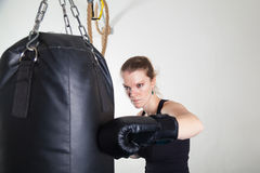 A young woman leans hands of black punching bag Royalty Free Stock Image