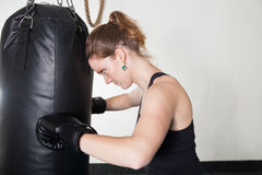 A young woman leans hands of black punching bag Royalty Free Stock Images