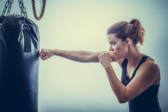 A young woman leans hands of black punching bag royalty free stock photography