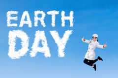 Young woman leaps with Earth Day text Royalty Free Stock Photos