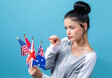 Flags of English speaking countries. Young woman with learn English theme with the flags of English speaking countries on a blue background stock photos