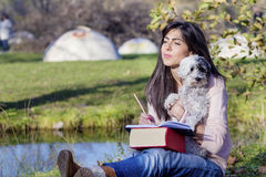 Young woman learning  with her dog in an autumn park Stock Image