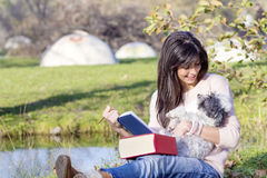 Young woman learning  with her dog in an autumn park Royalty Free Stock Photography