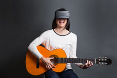 Young woman learning how to play the guitar through virtual real Royalty Free Stock Photography