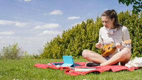 Young woman learning how to play ukulele from a digital tablet tutorial Royalty Free Stock Image