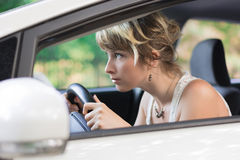 Young Woman Learning to Drive Car and Leaning Royalty Free Stock Image