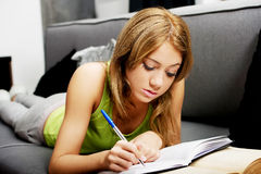 Young woman learning to exam on a sofa. Stock Photos