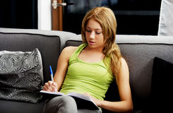Young woman learning to exam on a sofa. Stock Image